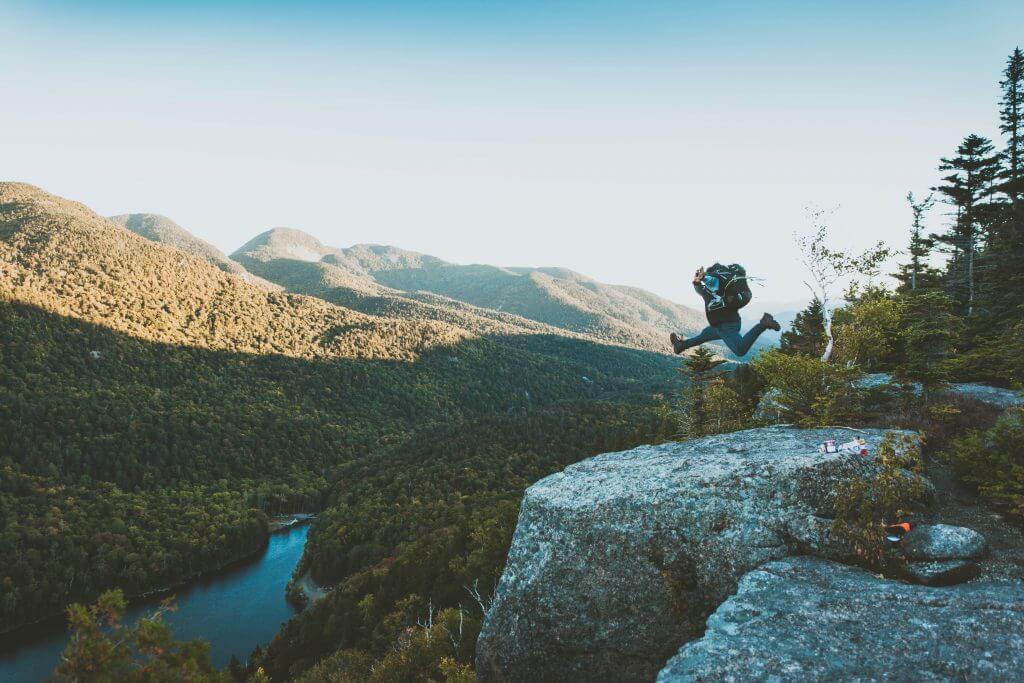 Reisender springt im Gebirge