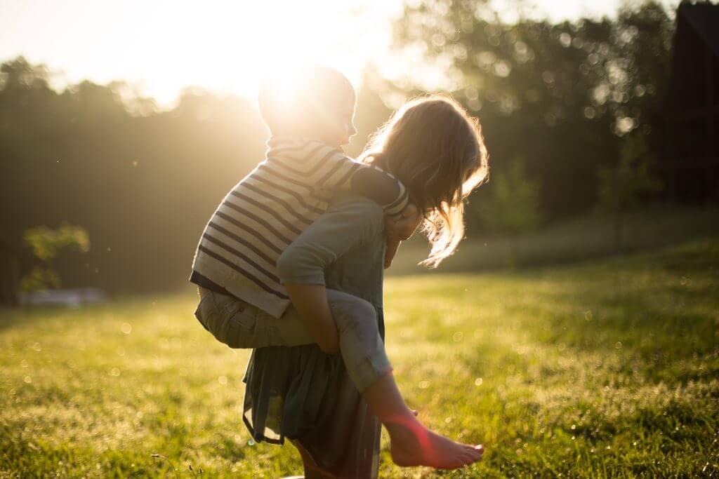Kinder tragen auf dem Rücken